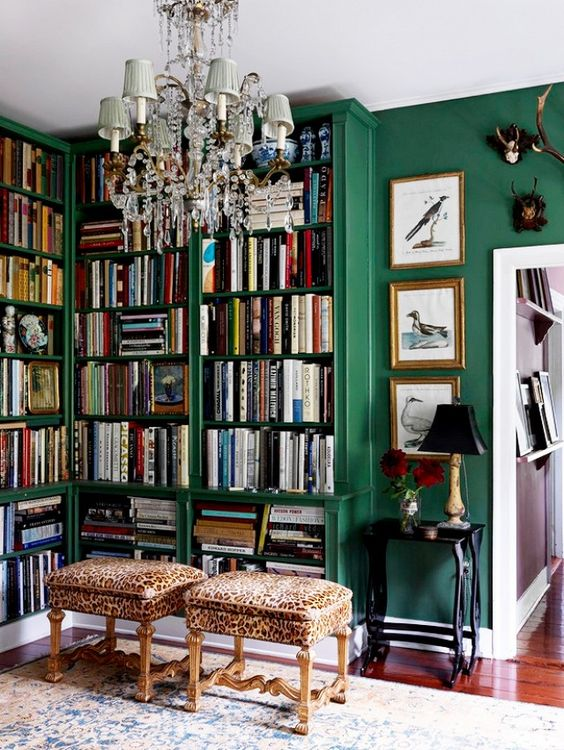 Emerald green built-in bookshelves home library with chandelier and library stools ottomans