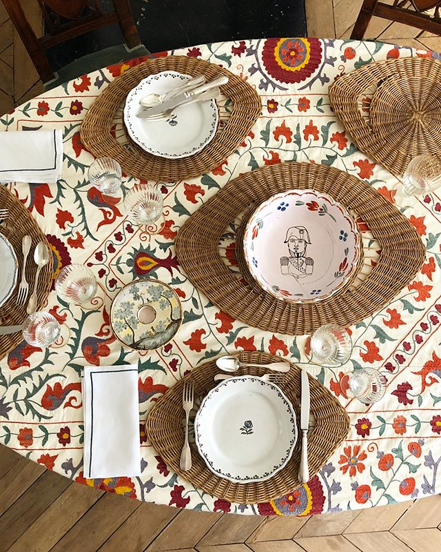 Vintage red suzani tablecloth with rattan eye placemats. French table setting.