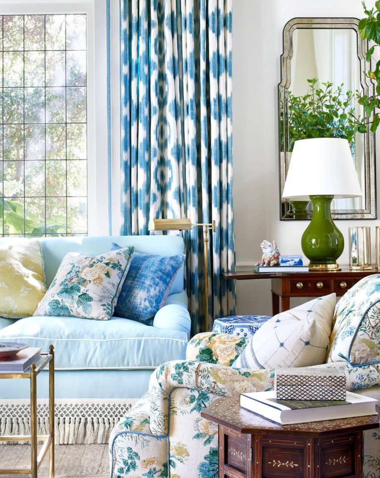 Montecito home decorated by Mark D. Sikes with blue and white ikat curtains and an armchair in Lee Jofa's Althea floral chintz