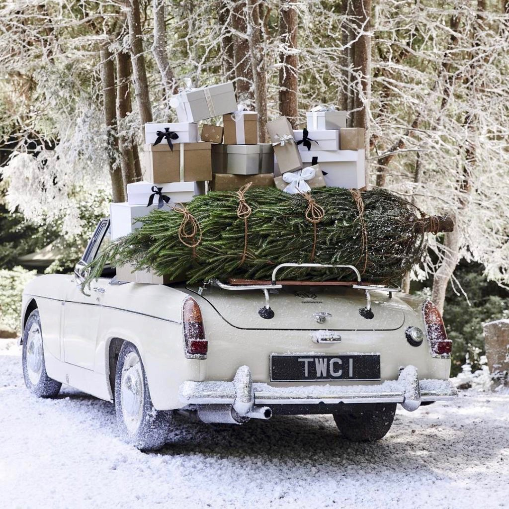 Vintage White Convertible Car with Christmas Tree and Presents in the Snow