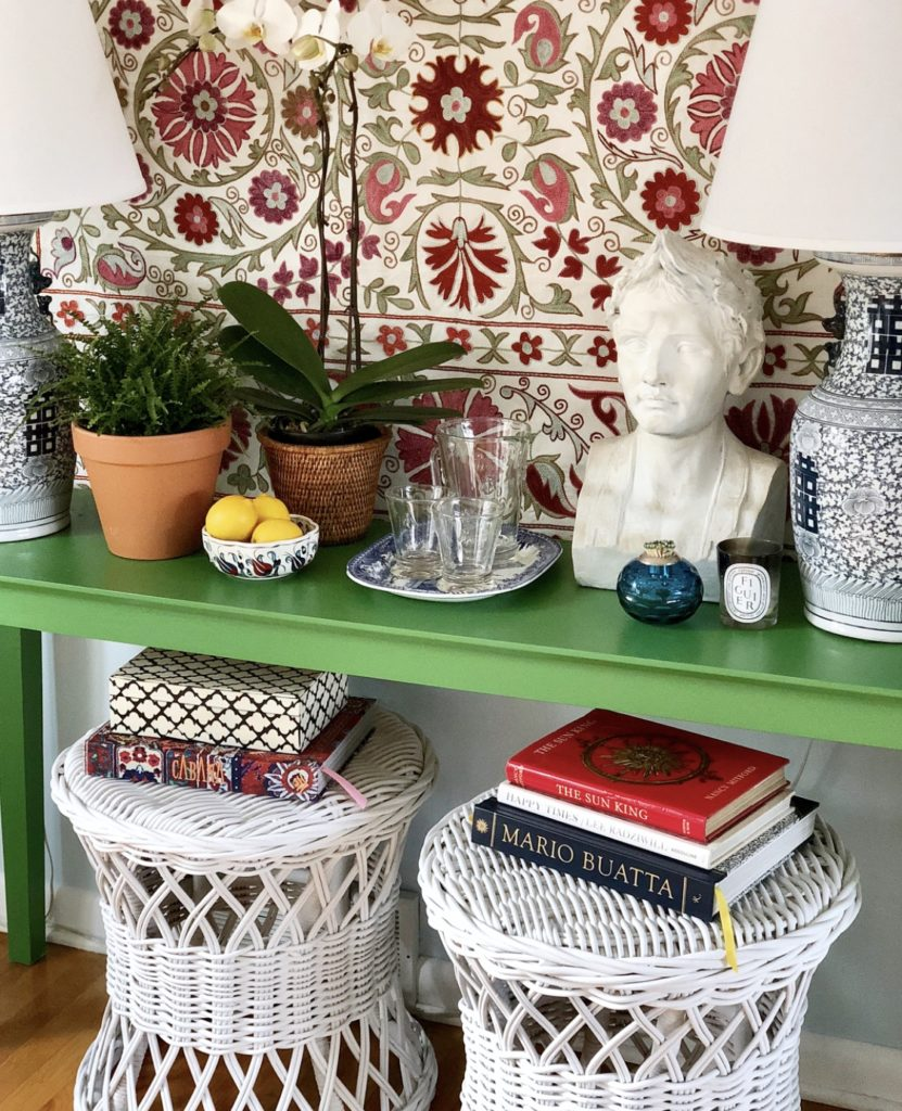 Green Console Table with Suzani Wall Hanging and Pair of White Wicker Ottomans