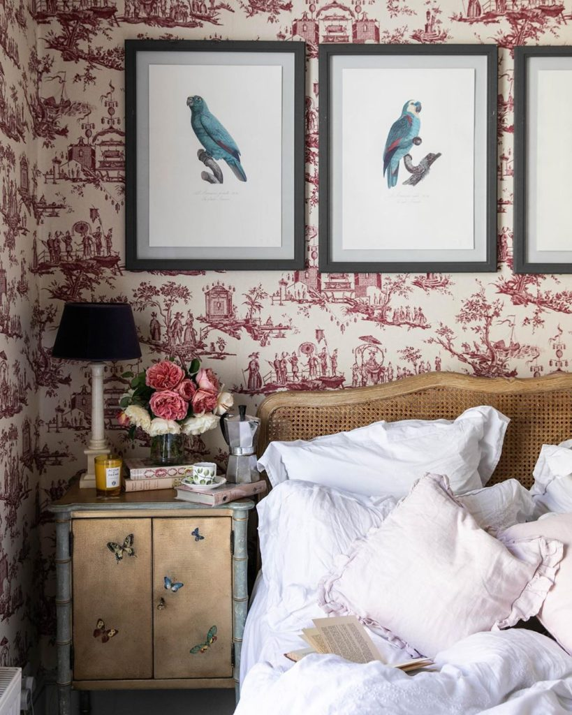 Skye McAlpine Bedroom with Red and White Toile Wallpaper Cane Headboard Parrot Bird Art Prints