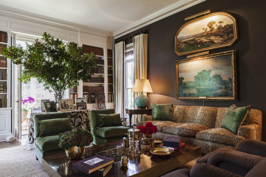 Aerin Lauder at home in her East Hampton living room on a leopard print sofa. Chocolate brown painted walls.