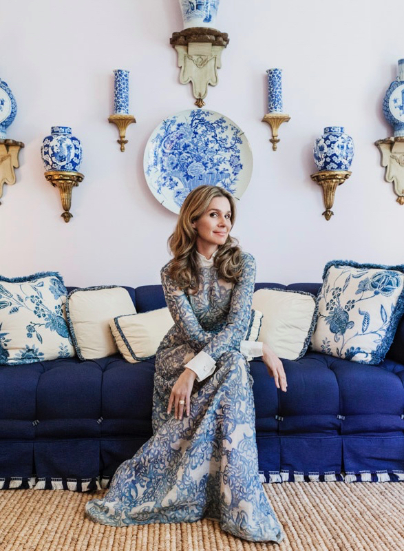 Aerin Lauder in her East Hampton home on a sofa in her Living Room with Lilac walls and blue and white Chinese porcelain displayed on the wall.