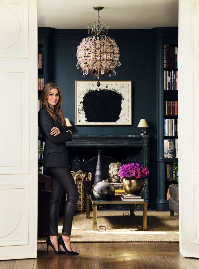 Aerin Lauder in her New York City Apartment Library with the Heather Chandelier and inky charcoal navy painted walls. Marble fireplace, sisal rug, brass coffee table.