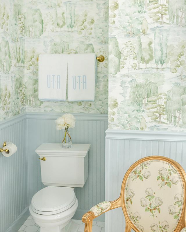 Bathroom with blue wainscoting and green scenic Sanderson wallpaper, monogrammed Weezie towels, and a Colefax and Fowler Bowood print chair by Tori Alexander of Alexander Interiors in Nashville.
