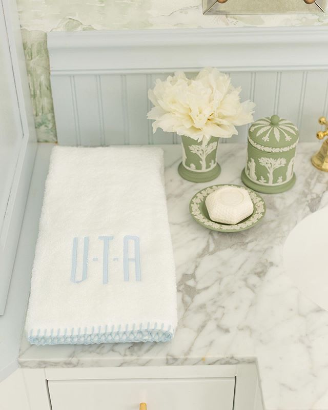 Bathroom with blue wainscoting, green Wedgwood Jasperware accessories, and monogrammed Weezie towels by Tori Alexander of Alexander Interiors in Nashville.