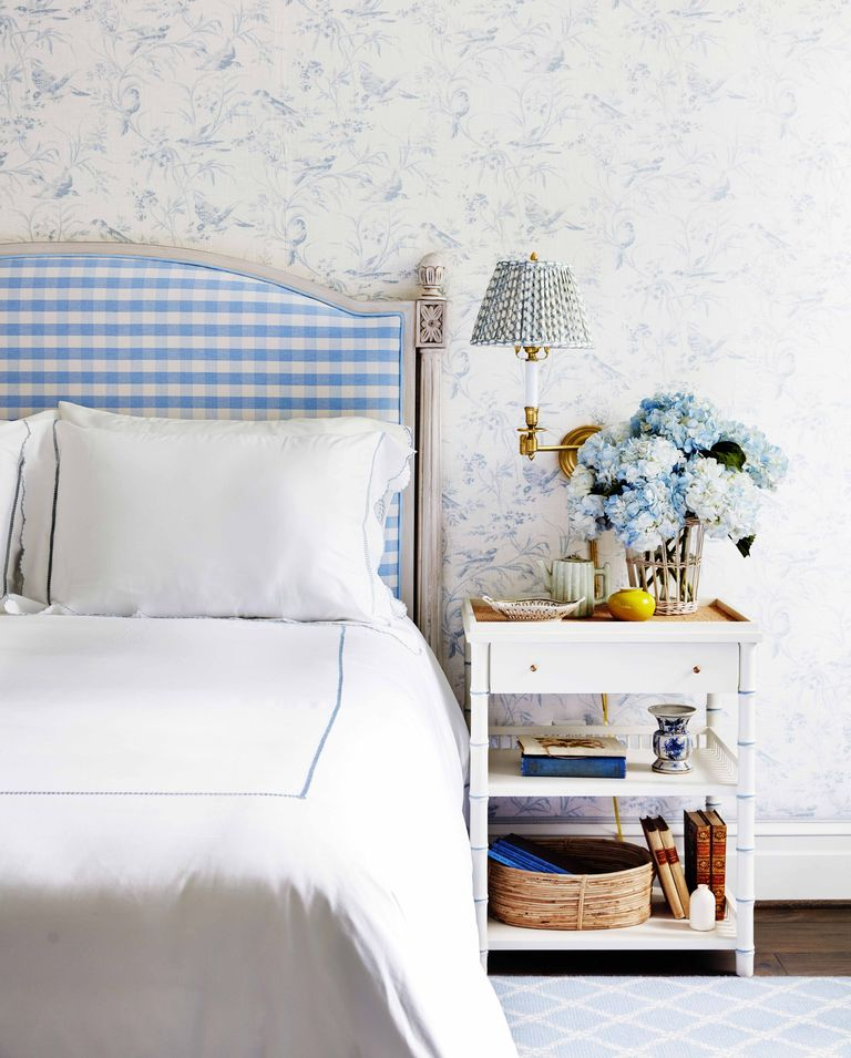 Blue and white toile wallpaper in a  bedroom decorated by Amy Berry Interior Design. Love the blue and white gingham upholstered headboard and bamboo nightstand.