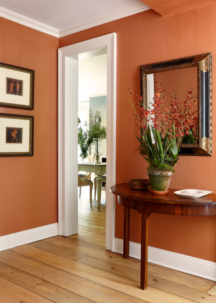Persimmon orange walls in a vestibule. Demilune table. Decorated by McGrath II.