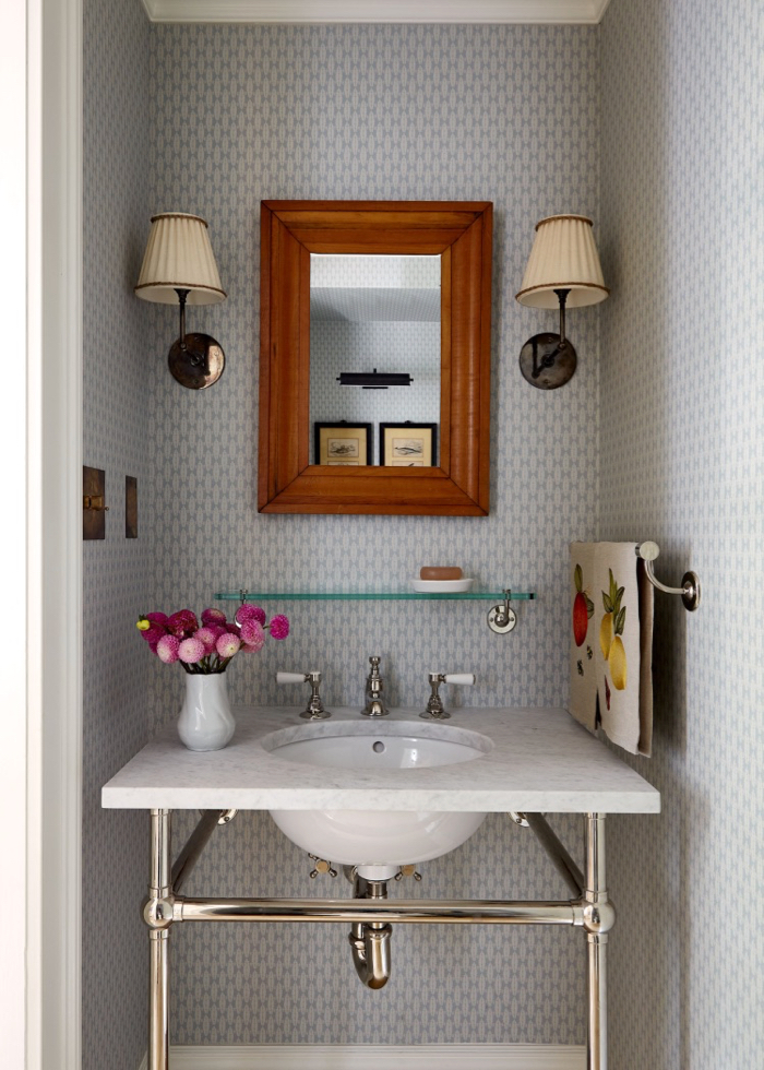 Powder room with wallpaper and sconces. Chrome vanity with marble counter. Glass shelf. Decorated by McGrath II.