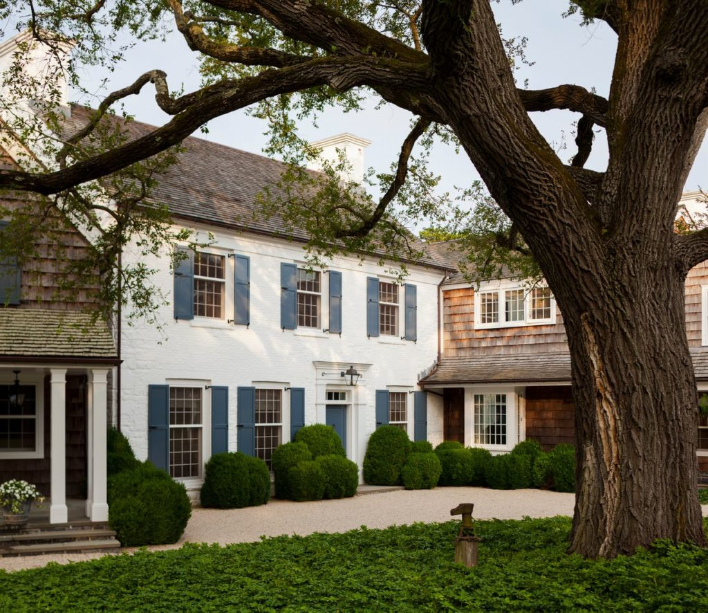 White brick house with navy blue shutters and front door and pea gravel driveway. Hamptons, New York.
